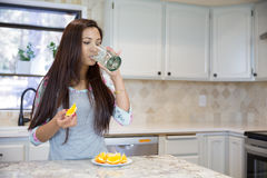 Beautiful brunette drinking water from glass at the kitchen.  Royalty Free Stock Image