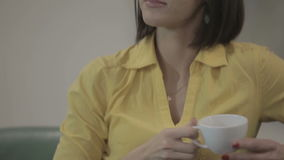 Beautiful brunette drinks a tea in the hotel on the green sofa. Close-up. Camera moves from down to up. Young brunette in yellow shirt sitting on the green stock video