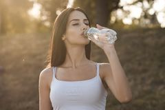 Beautiful brunette drinks water from a bottle royalty free stock images