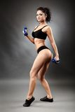 Beautiful brunette with dumbbells on gray background Royalty Free Stock Images