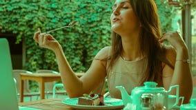 Beautiful brunette eating cheesecake stock video footage