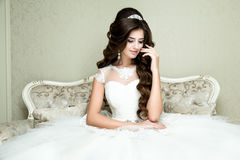 Beautiful brunette elegant Bride with wedding makeup and hairstyle with diamond crown sitting in vintage armchair. Royalty Free Stock Photo
