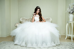 Beautiful brunette elegant Bride with wedding makeup and hairstyle with diamond crown sitting in vintage armchair. Royalty Free Stock Photos
