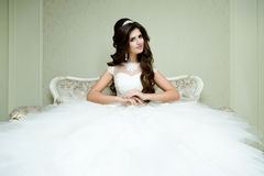Beautiful brunette elegant Bride with wedding makeup and hairstyle with diamond crown sitting in vintage armchair. Fashion bride model jewelry and beauty Stock Photo