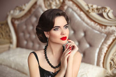 Beautiful brunette, elegant woman portrait. Manicure nails. Retro lady with red lips makeup, wavy hairstyle posing on modern bed. In bedroom interior royalty free stock images