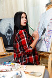 Beautiful brunette engaged in painting Stock Images
