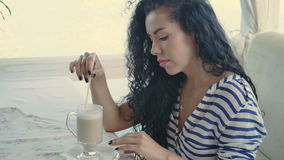 Beautiful brunette enjoy of drinking latte. Beautiful brunette sits at summer terrace and relax. Cute woman straightens her curly hair and drinks a coffee stock footage