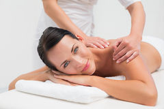 Beautiful brunette enjoying a back massage smiling at camera Stock Photo