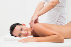 Beautiful brunette enjoying a back massage smiling at camera Stock Image