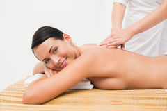 Beautiful brunette enjoying a back massage smiling at camera Royalty Free Stock Photo