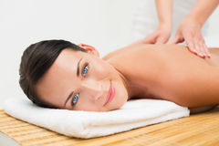 Beautiful brunette enjoying a back massage smiling at camera Royalty Free Stock Photography