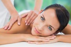 Beautiful brunette enjoying a back massage smiling at camera Royalty Free Stock Image