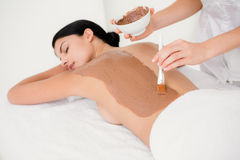 Beautiful brunette enjoying a chocolate beauty treatment Stock Photos