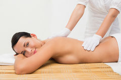 Beautiful brunette enjoying an exfoliating back massage smiling at camera Royalty Free Stock Photo