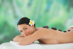 Beautiful brunette enjoying hot stone massage smiling at camera Royalty Free Stock Photo