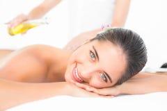 Beautiful brunette enjoying an oil massage. Close up plan of beautiful brunette enjoying an oil massage at the health spa stock photos