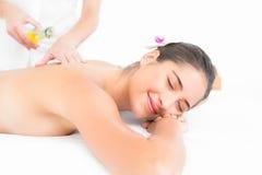 Beautiful brunette enjoying an oil massage. At the health spa stock photos