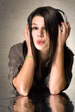 Beautiful  brunette enyjoying music in headphones. Royalty Free Stock Images
