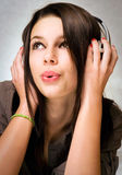 Beautiful brunette enyjoying music in headphones. Stock Images