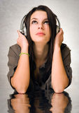 Beautiful brunette enyjoying music in headphones. Royalty Free Stock Photography