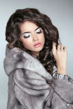 Beautiful brunette Fashion girl in Mink Fur Coat isolated on gra Royalty Free Stock Photo