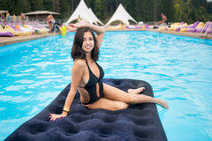Beautiful brunette female in black bikini lying on an inflatable mattress in swimming pool at the resort. In focus with blurred background royalty free stock image