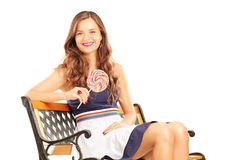 Beautiful brunette female sitting on bench and holding a lollipop Stock Image