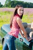 Beautiful brunette female standing near car Stock Photos