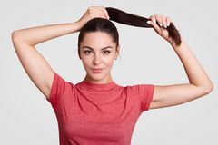 Beautiful brunette female touches pony tail, has healthy skin, dressed in casual t shirt, has make up, rests at home, shows her na stock photography