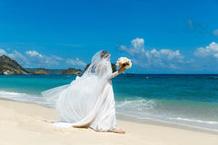Beautiful brunette fiancee in white wedding dress with big long. White train and with wedding bouquet stand on shore sea near the wedding arch of vines and royalty free stock photos