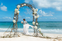 Beautiful brunette fiancee in white wedding dress with big long. White train and with wedding bouquet stand on shore sea near the wedding arch of vines and Stock Photography
