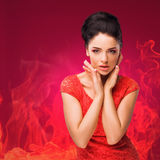 Beautiful brunette on a fiery background. Stock Photo