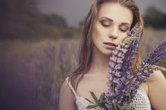Beautiful brunette fit slim fragile woman with clear flawless sk. In and waved hair in sensual summer dress in the middle of meadow lupins field on a sunset Royalty Free Stock Photo