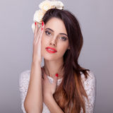 Beautiful brunette with flowers in head and red lipstick Stock Photography
