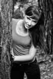 Beautiful brunette in a forest. Beautiful brunette in a red shirt posing next to a tree, in a nature, fashion photography, black and white photo Royalty Free Stock Photography