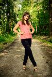 Beautiful brunette on a forest road. Beautiful brunette in a red shirt and jeans posing on a forest road, in a nature, fashion photography Royalty Free Stock Photography
