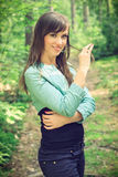 Beautiful brunette on a forest road. Beautiful brunette in a shirt and jeans posing on a forest road, in a nature, fashion photography Royalty Free Stock Photos