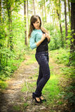 Beautiful brunette on a forest road. Beautiful brunette in a shirt and jeans posing on a forest road, in a nature, fashion photography Stock Image