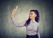 Beautiful brunette in formal outfit using smartphone and taking selfie on gray background royalty free stock photos