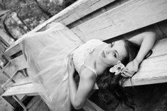 Beautiful brunette in a gazebo. Beautiful brunette in white dress lying on a bench in a gazebo, fashion photography, black and white photo Royalty Free Stock Image