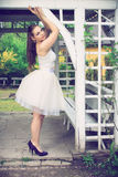 Beautiful brunette at the gazebo. Beautiful brunette in white undershirt and white scarf and heel shoes posing at the gazebo in exterior, fashion photography Stock Photography