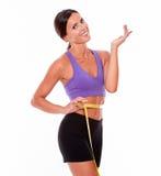 Beautiful brunette gesturing measuring her waist Stock Photo