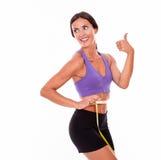 Beautiful brunette gesturing measuring her waist Royalty Free Stock Photos