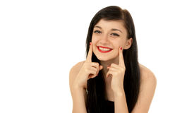 Beautiful brunette girl. Beautiful  smiling brunette girl wearing a black dress putting her fingers to her cheeks on white background Royalty Free Stock Photography
