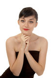 Beautiful brunette girl. Beautiful  brunette girl wearing a black dress putting her hands to the face and  looking directly at the camera on white background Royalty Free Stock Photography