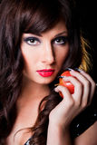 Beautiful brunette girl with apple on black Royalty Free Stock Image