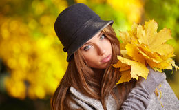 Beautiful brunette girl in autumn park. Warm sunny da Royalty Free Stock Photos