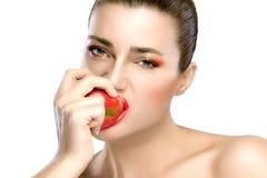 Beautiful Brunette Girl Biting an Apple Royalty Free Stock Photos