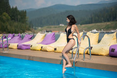 Beautiful brunette girl in black bikini who enters the water in the pool on mountain resort. On the background of hills and forest in the distance Stock Photography