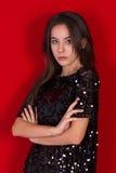 Beautiful brunette girl in a black dress. Brunette with long black hair Stock Image